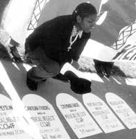 A woman at a CCWP demonstration, with cardboard tombstones of five women who died of medical neglect while at CCWF.